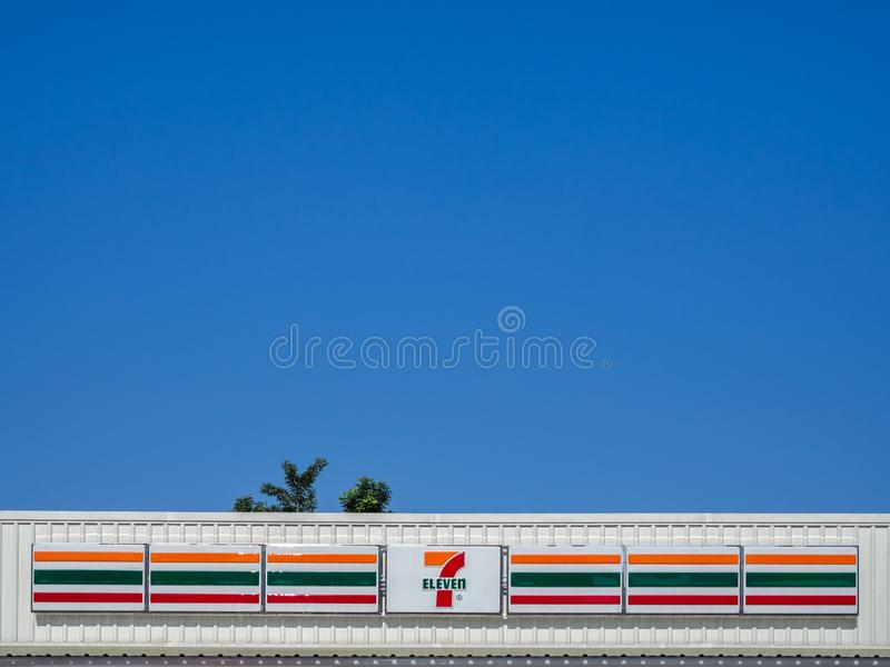 7-Eleven在白色商店屋顶的标志有在天空蔚蓝backgrou的树的 库存图片
