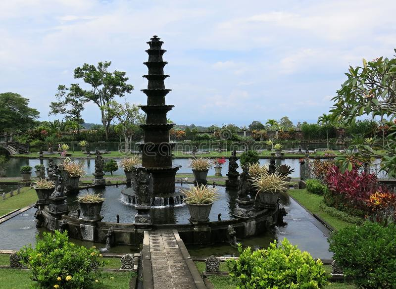 Eleven-levels fountain in the water palace. Promenade in tropical garden. Tropical garden with palm and many colorful flowers. royalty free stock photos