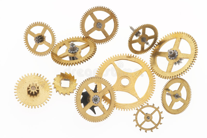 Eleven old cogwheels. Many old gold-coloured little cogwheels are connected stock photos