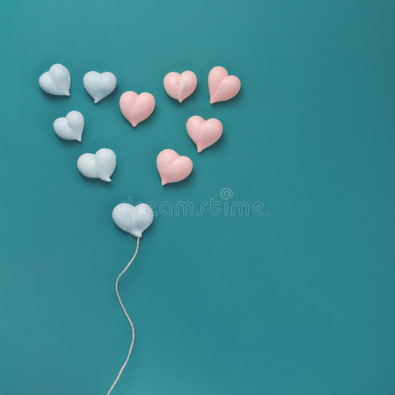 Eleven small meringues of pink and blue hearts are laid out in big heart with with rope made of natural twine like royalty free stock photography
