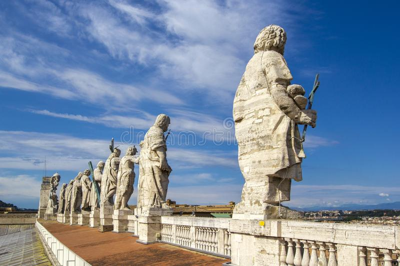 Eleven statues of the saints apostles standing on the roof of Saint Peter`s Basilica in Vatican City, Rome, Italy, back view royalty free stock photos