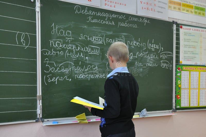 Eleven utför uppgiften på skolförvaltningen på kursen av det ryska språket royaltyfri foto