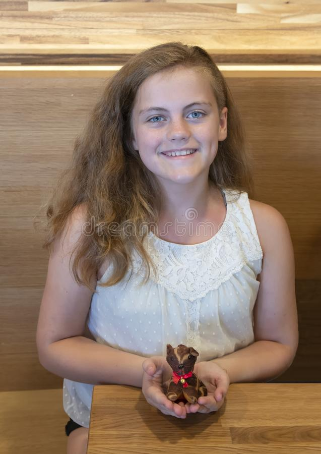 Eleven year-old Caucasian girl holding a small stuffed animal in a restaurant in Seattle, Washington. Pictured is a happy smiling 11 year-old Caucasian girl stock photography