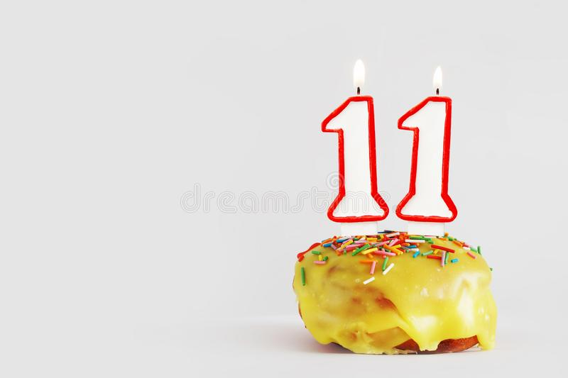 Eleven  years anniversary. Birthday cupcake with white burning candles with red border in the form of number Eleven. Light gray background with copy space stock image