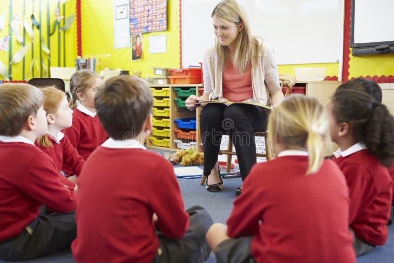 Elever för lärareReading Story To grundskola royaltyfri foto