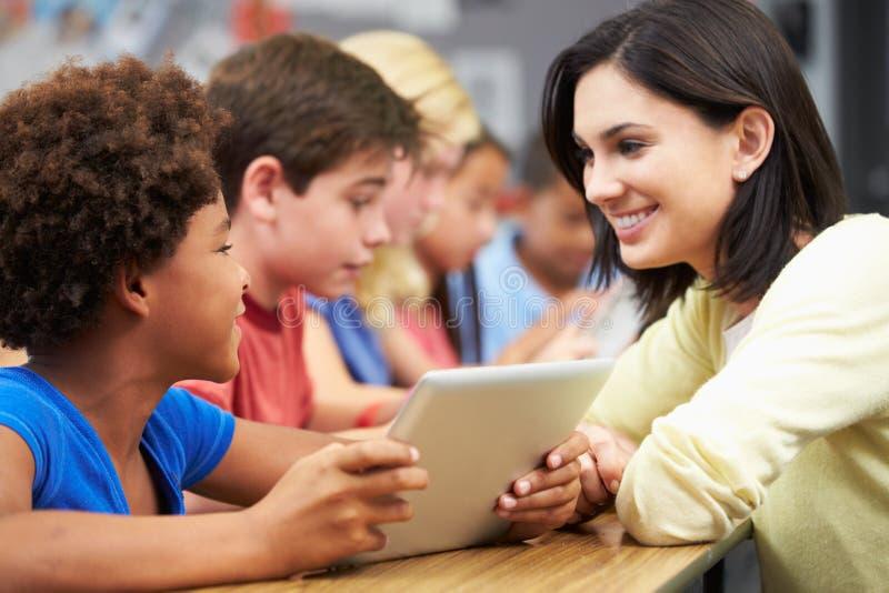 Elever i grupp som använder den Digital minnestavlan med läraren royaltyfria bilder