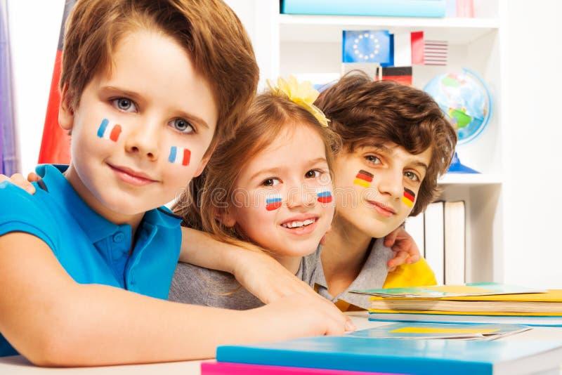 Elever med flaggor på kinder som sitter på skrivbordet arkivbilder