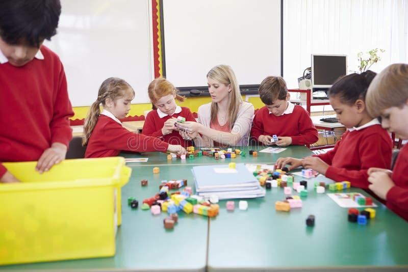 Elever och lärareWorking With Coloured kvarter royaltyfri bild