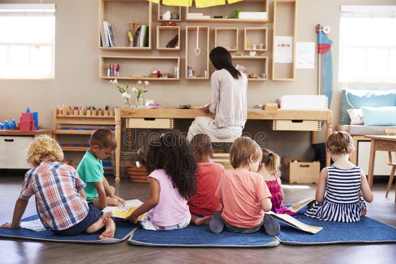 Elever på den Montessori skolan som självständigt läser i klassrum fotografering för bildbyråer