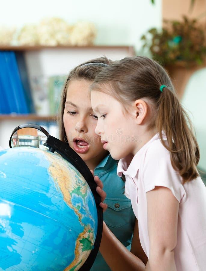 Elever ser jordklotet i wide-eyed häpnad arkivbilder