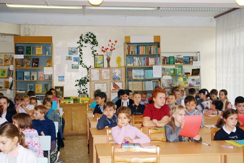 Elever sitter i grupp på deras skrivbord royaltyfri fotografi
