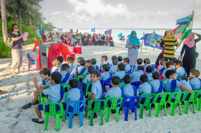 Elever som sitter på stranden royaltyfria bilder
