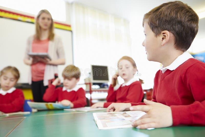 Elever som sitter på tabellen som läraren Stands By Whiteboard royaltyfri fotografi