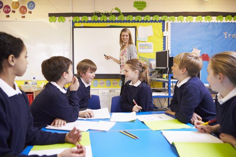 Elever som sitter på tabellen som läraren Stands By Whiteboard royaltyfria bilder