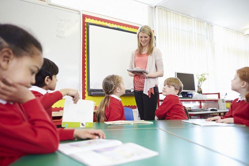 Elever som sitter på tabellen som läraren Stands By Whiteboard royaltyfri foto