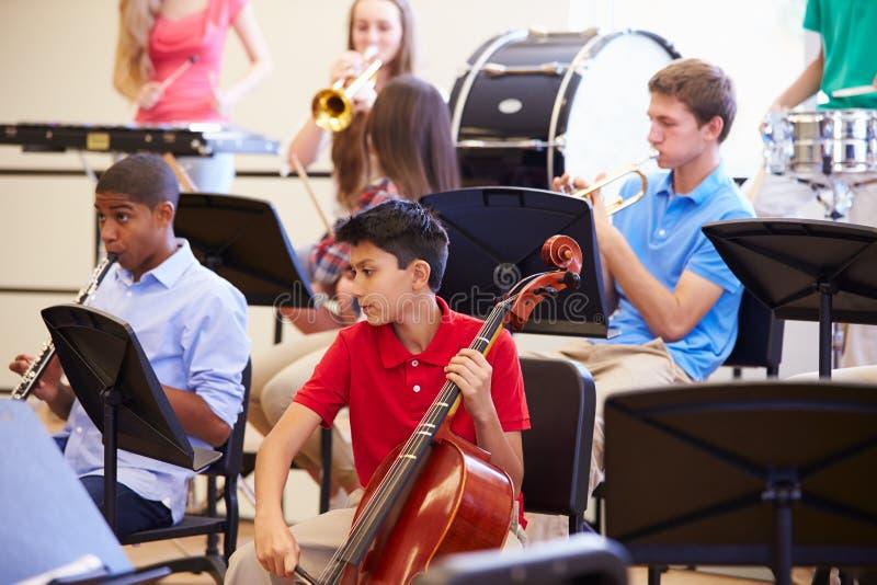 Elever som spelar musikinstrument i skolaorkester royaltyfri fotografi