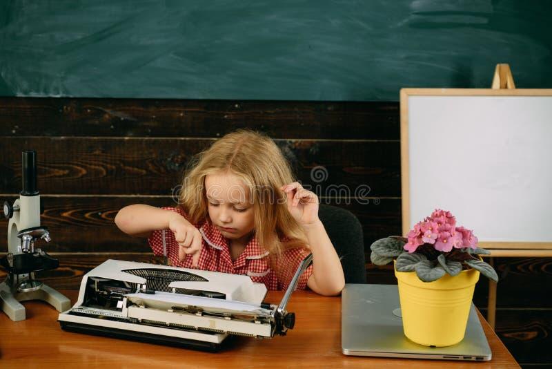 Elevtyp på skrivmaskinen i skolagrupp Grundskolaeleven tycker om att lära att skriva på maskin royaltyfria foton