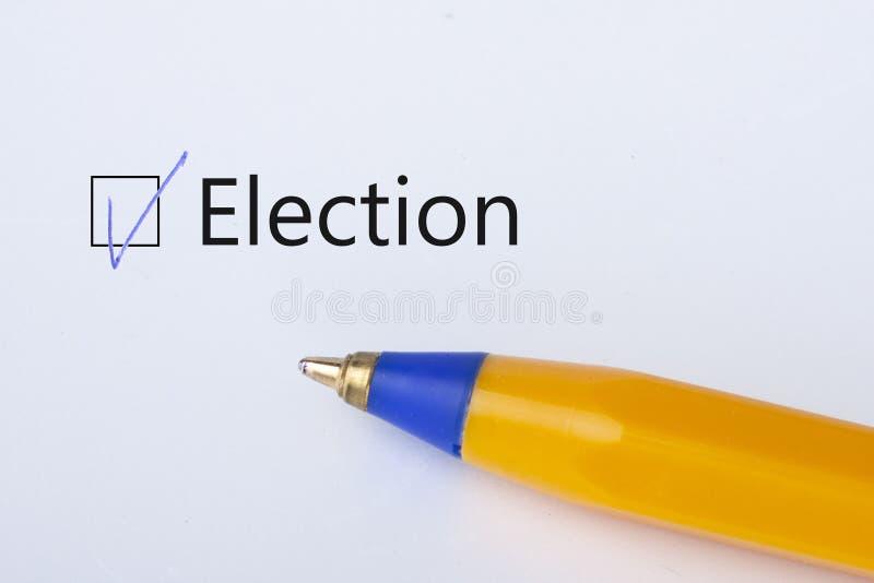 Elezione - casella di controllo con un segno di spunta su Libro Bianco con la penna gialla Concetto della lista di controllo immagine stock