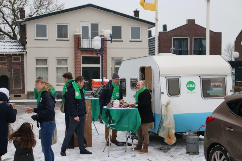 Elezioni Paesi Bassi 2018 della giunta comunale: Membro di CDA che dà i presente via per vincere un elettore in Zevenhuizen immagine stock