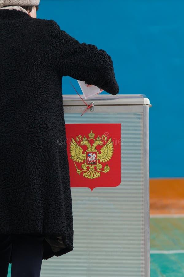 Elezioni presidenziali russe - una donna mette una scheda elettorale alla scatola di voto fotografie stock