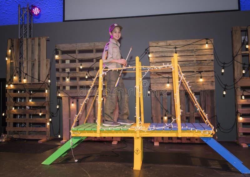 Elf éénjarigenjongen in eenvormig verkennen kruisend de brug, Pijl van Lichte Ceremonie stock fotografie