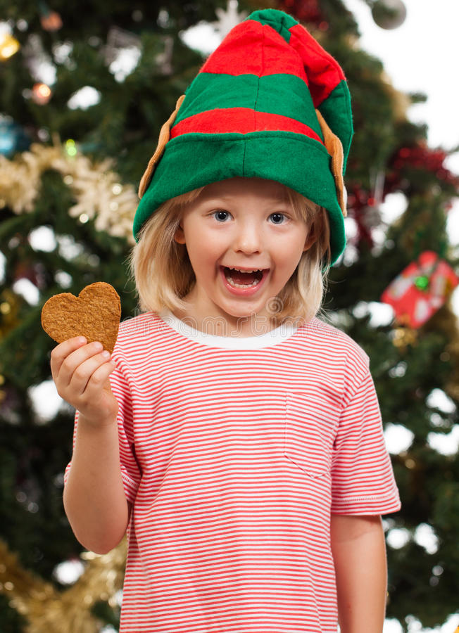Elf boy holding gingerbread cookie stock images