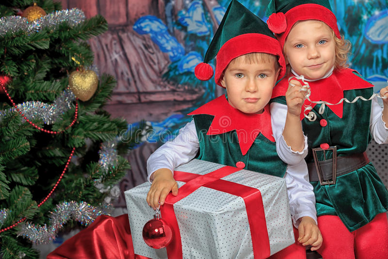 Elf children. Two cute children in christmas elf costumes posing over christmas background royalty free stock photos