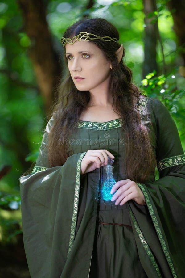Elf con una bottiglia di pozione magica fotografia stock libera da diritti