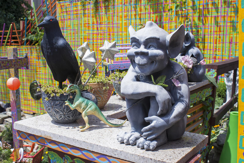 Gremlin and Crow. Smiling Gray Gremlin with Large Pointed Ears Sits on a Wall Next to a Large Black Crow and a Green and Yellow Dinosaur stock image