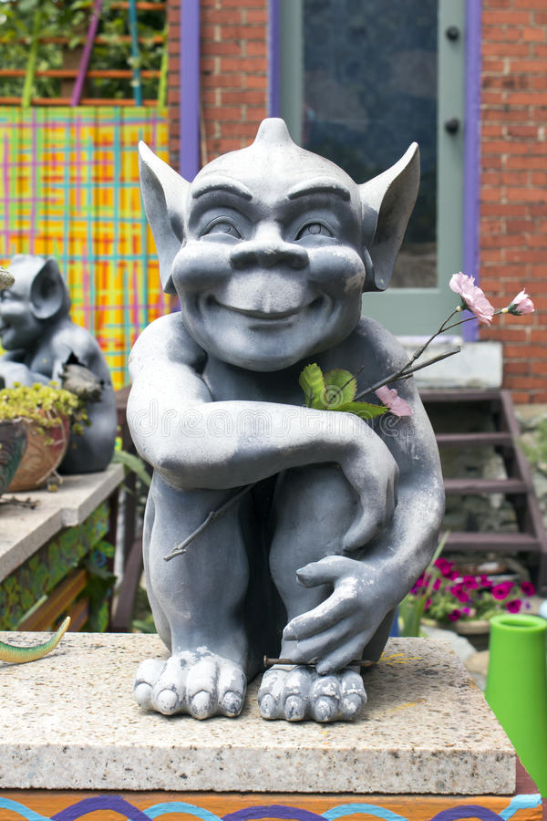 Gremlin and Flower. Smiling Gray Gremlin with Large Pointed Ears Sits on a Wall While Holding a Long Stem Pink Flower royalty free stock images