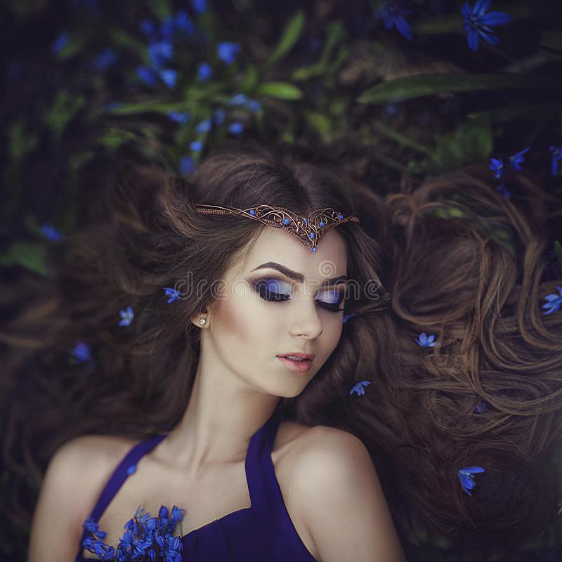 Elf girl with long hair in the tiara rests in spring forest blue forest flowers. Girl Princess dreams. Creative colors and Artistic processing stock photography