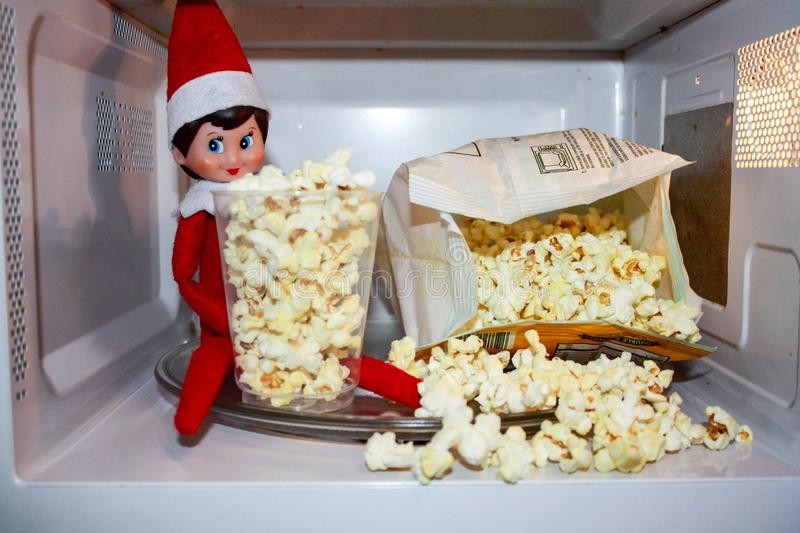 Elf on the shelf. Making popcorn from the North Pole royalty free stock image