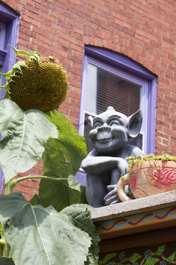 Gremlin and Sun Flower. Smiling Gray Gremlin with Large Pointed Ears Sits on a Wall Next to a Large Yellow Sun Flower and a Giant Tea Cup stock photography