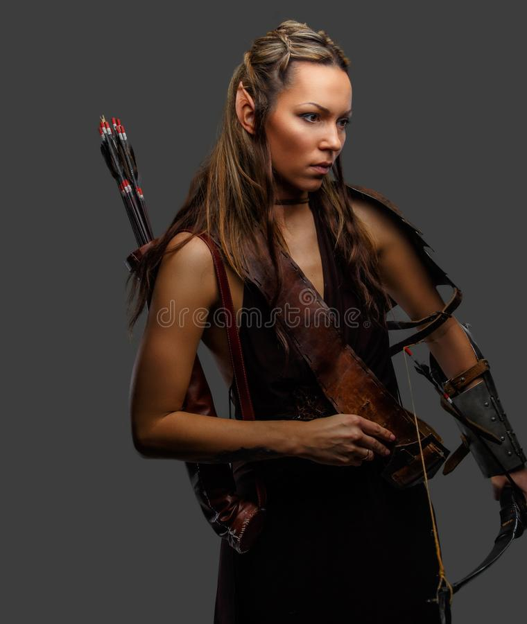 A woman with bow. Elf woman in armour with bow isolated on a grey background stock photography