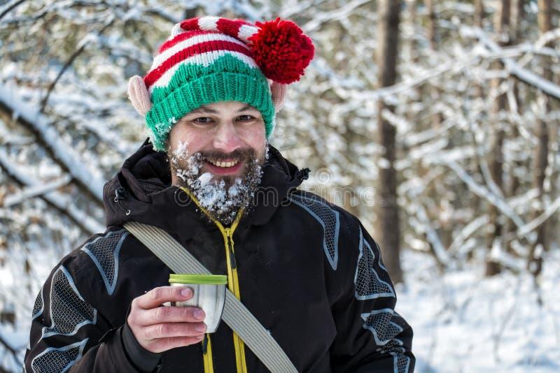 elfe Neige-barbu de Noël tenant une tasse de thé chaud et de rire images libres de droits