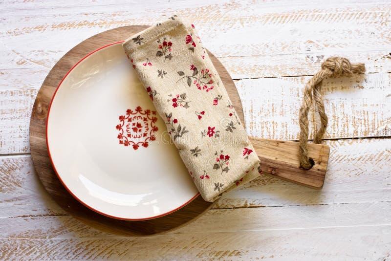 Elfenbeinfarbene leere Platte mit rotem Brett auf rundem Schneidebrett, Leinenblumenserviette, hölzerner Hintergrund der weißen P stockfoto