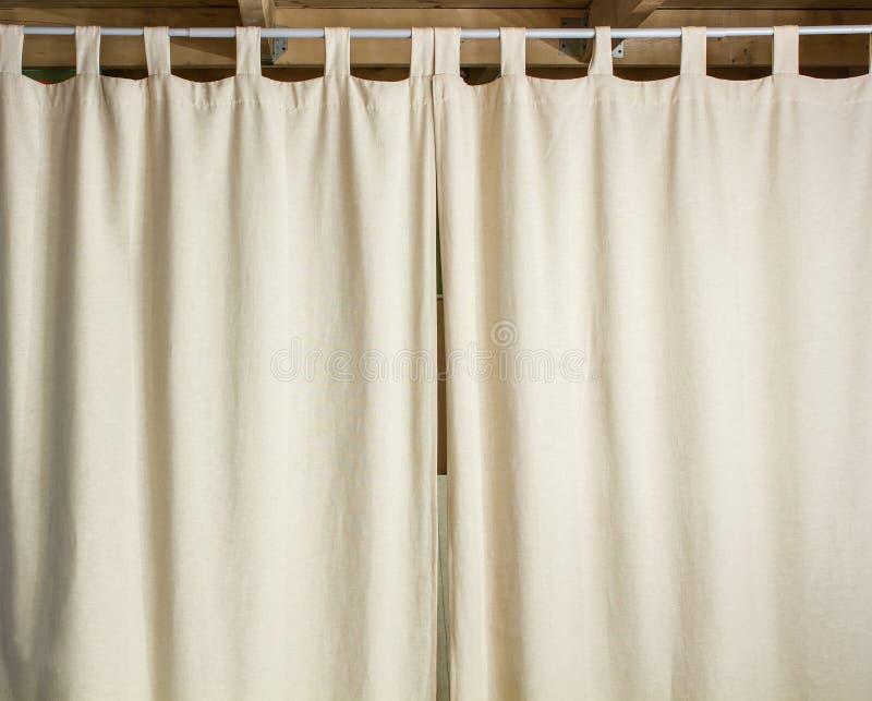 Elfenbeinvorhang, der an einer Metallstange hängt stockbild