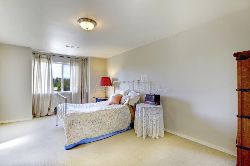 Elfenbeinwandschlafzimmer mit weißem Eisenbett und rote Lampe auf dem nightstand stockbilder