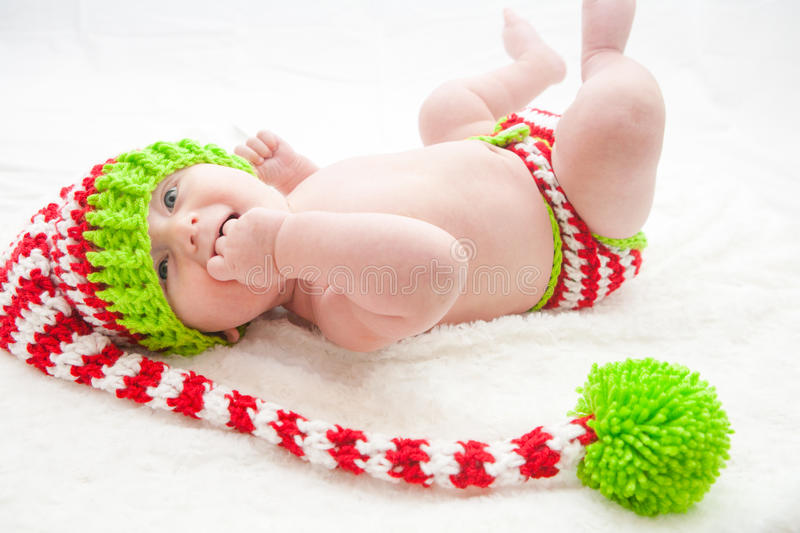 Elfish Christmas Baby. Baby wearing red white and green striped knit hat and diaper cover stock photo