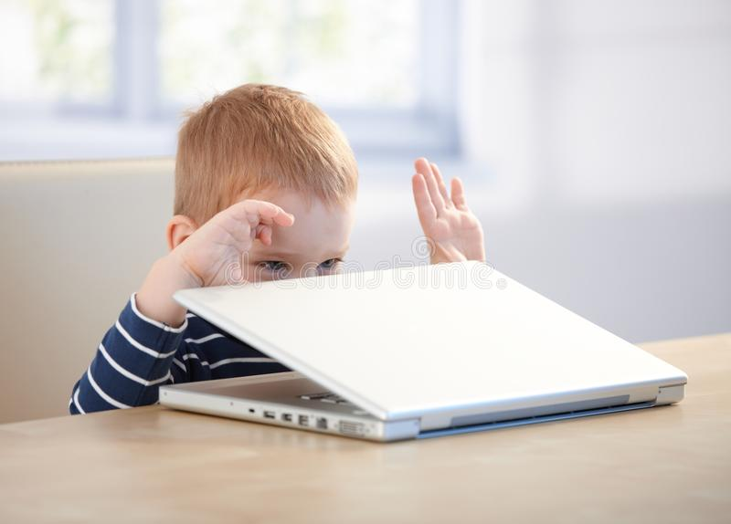 Elfish little boy playing with laptop. Elfish little boy sitting at table having fun with laptop stock photography