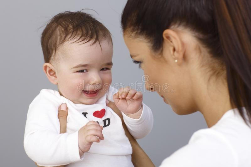 Elfish little boy playing with mother. Elfish little boy smiling in mother's arms stock photos
