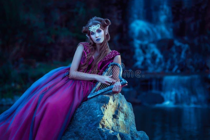 Elfvrouw in violette kleding stock fotografie