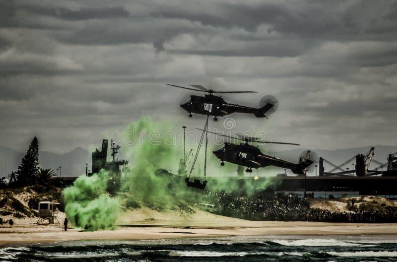 Elicotteri di Thow sopra una spiaggia immagine stock