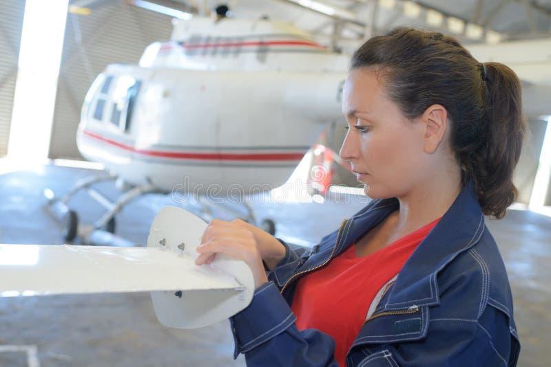 Elicottero in capannone e nel funzionamento femminile dell'ingegnere immagine stock libera da diritti