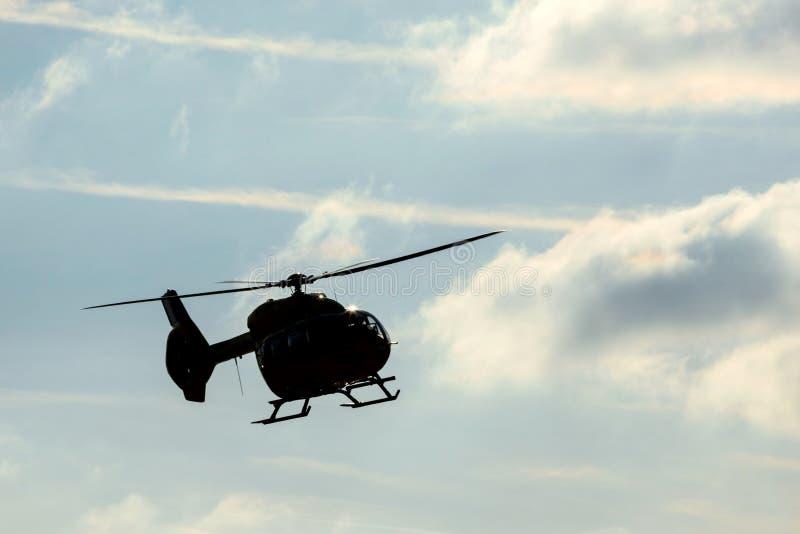 Elicottero in volo con le nuvole fotografie stock