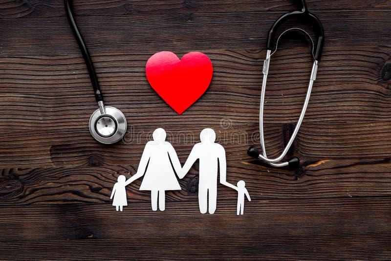 Elija el seguro médico de la familia Estetoscopio, corazón de papel y silueta de la familia en la opinión superior del fondo de m fotos de archivo libres de regalías