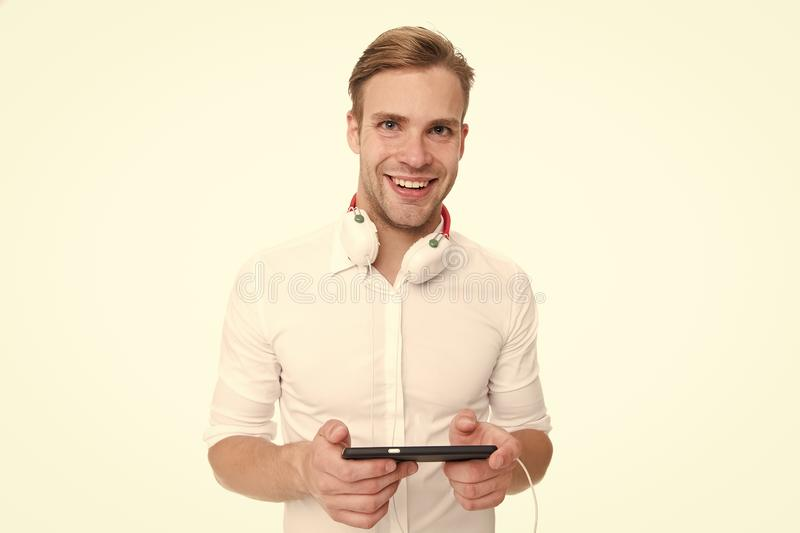 Elija la estación de radio Sirva la canción preferida que escucha en auriculares con smartphone y el canto El hombre disfruta de  imágenes de archivo libres de regalías