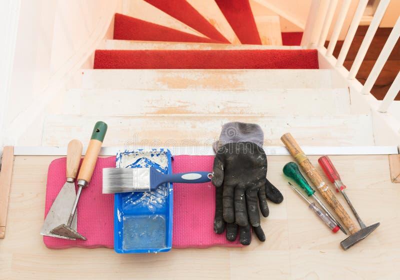 Eliminación de la alfombra, del pegamento y de la pintura de las escaleras de un vintage imagen de archivo libre de regalías