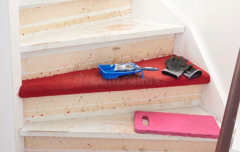 Eliminación de la alfombra, del pegamento y de la pintura de las escaleras de un vintage foto de archivo