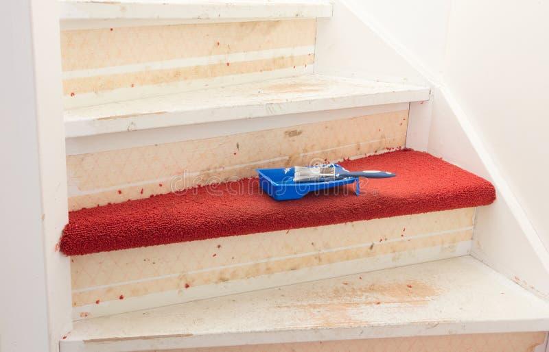 Eliminación de la alfombra, del pegamento y de la pintura de las escaleras de un vintage imagen de archivo